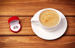 Wedding ring in a red box and cup of coffee Stock Images