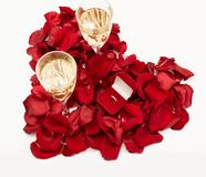 Wedding ring red box surrounded by rose petals. An offer of marriage. Heart-shaped rose petals. White gold engagement ring with diamonds in a heart shaped box stock image