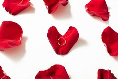 Wedding ring red box surrounded by rose petals. An offer of marriage. White gold engagement ring with diamonds in a heart shaped box and roses on white isolated royalty free stock image