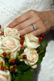 Wedding ring and rose bouquet. Close-up of bride holding bouquet with wedding rings visible Stock Image