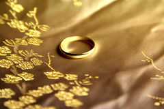 Wedding ring on silk. Golden chinese silk as background for golden wedding ring stock photos