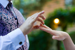 Wedding ring - symbol of love. Hands of bride and groom close-up - they exchange rings Royalty Free Stock Image