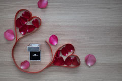 Wedding ring and two red heart ribbon with pink and red rose petals on wooden surface with empty space for text Royalty Free Stock Image