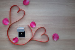 Wedding ring and two red heart ribbon with pink rose petals on w Stock Photo