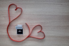 Wedding ring and two red heart ribbon on wooden surface with empty space for text Royalty Free Stock Images