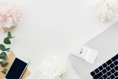 Wedding ring in white gift box on background of flowers and phone. top view Royalty Free Stock Photo