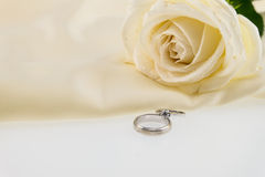 Wedding ring and white rose on ivory silk satin Stock Images