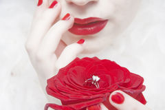 Wedding ring woman. Woman with diamond wedding ring in red rose stock images