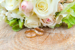 Wedding ring on wooden ground with wedding bouquet Royalty Free Stock Photography