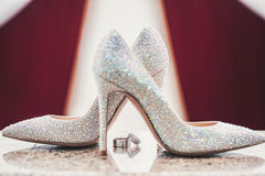 Wedding-ring and woomen shoes acute Royalty Free Stock Images