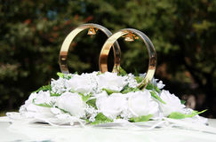 Wedding rings. Two wedding rings with bells in the white flowers Stock Images