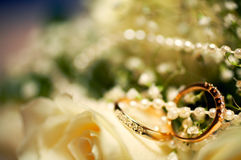 Wedding rings. Golden wedding rings with precious stones on a blur background of flowers and beads Stock Image