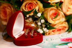 Wedding rings. Golden wedding rings in a red box on a background of beautiful flowers Stock Images