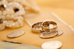 Wedding rings. Silver and gold weddings rings with coins and flowers Royalty Free Stock Images