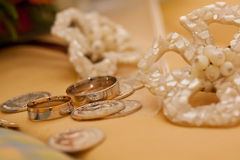 Wedding rings. Silver and gold weddings rings with coins and flowers Stock Image