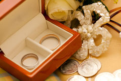 Wedding rings. Silver and gold weddings rings with coins and flowers Stock Images