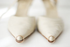 The wedding rings. On the bride's shoes Royalty Free Stock Photos