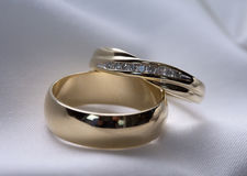 Wedding rings. Closeup of gold wedding rings on a white satin background Stock Image