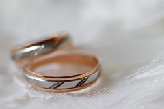 Wedding rings. Two golden wedding rings on a blurred white fabric background Stock Photo