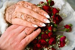 Wedding rings. Hands of the groom and the bride with wedding rings on top of the bride's bouquet Stock Images