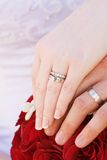 Wedding rings. A couples hands on a bouquet of red roses Royalty Free Stock Photography