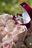 Wedding rings. On red roses bouquet Royalty Free Stock Photos