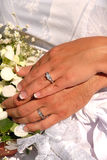 Wedding Rings. Husband and wife showing their wedding rings surrounded by the bride's bouquet Royalty Free Stock Photo