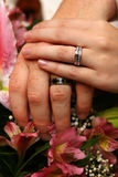Wedding rings. Bride and groom's hands and rings on bouquet stock photo