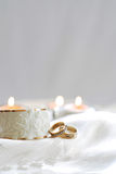 Wedding Rings on White. Gold wedding bands next to a white ceramic candle holder on a white silk cloth, three candles glowing in the background, space for text Stock Photos