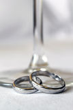 Wedding rings. Close up of two gold wedding  rings and glass Royalty Free Stock Image