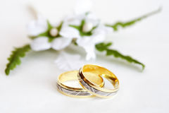 Wedding rings. With small flower on bright background Royalty Free Stock Photos