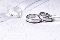 Wedding rings. Lovely white and grey gold wedding rings on a pillow royalty free stock images