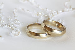 Wedding rings. Two wedding rings from yellow gold lie on a dress of the bride Stock Photos