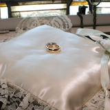 Wedding Rings. Pair of gold wedding rings arranged atop a ringbearer's satin and lace pillow Stock Photography