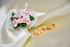 Wedding rings. Over ivory silk and bouquet Royalty Free Stock Photo