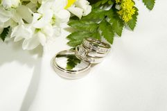 Wedding Rings. Wedding bands arranged near the edge of a bridal bouquet and a white piece of cloth Stock Photography