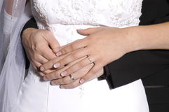 Wedding Rings. Bride and groom hands overlapping around the waist of the bride with wedding rings visible Stock Images