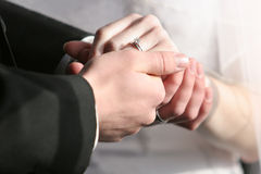 Wedding Rings. Couple holding hands in sunlight displaying wedding rings Stock Photos