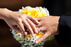 Wedding rings. Bride and groom hands with the wedding rings and wedding bouquet Royalty Free Stock Photo