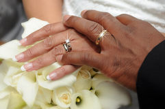 Wedding Rings. Bride and Groom display their wedding rings after the wedding ceremony over the Bridal Bouquet Royalty Free Stock Image