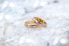 Wedding rings. Two gold wedding rings with precious stones lie on the white lace Stock Photo