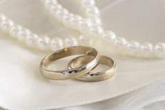 Wedding rings. On the textile white background with pearls Stock Image