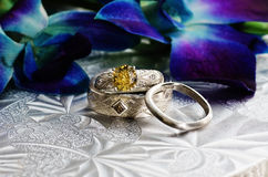 Jewelry:Wedding Rings, Flowers, Brocade Table Clot. Wedding rings on brocade, silver background with floral arrangement Royalty Free Stock Image