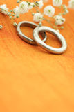 Wedding rings. With small flowers on orange silk background Stock Image