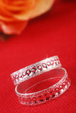 Wedding rings. Macro shot of wedding rings with rose in out of focus Royalty Free Stock Photo