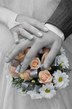 Wedding rings. On hands and bouquet stock image