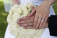 Wedding rings. Bride and groom holding wedding rings on top of bride's bouquet Royalty Free Stock Photo
