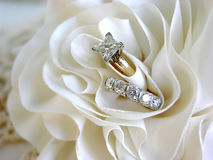 Wedding Rings. Diamond wedding rings in the folds of the bride's dress Stock Images