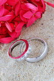 Wedding Rings. His And Hers Wedding Rings In The Sand With Red Flowers Royalty Free Stock Photo