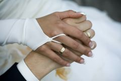 Wedding rings. Holding hands of bride and groom Stock Photos